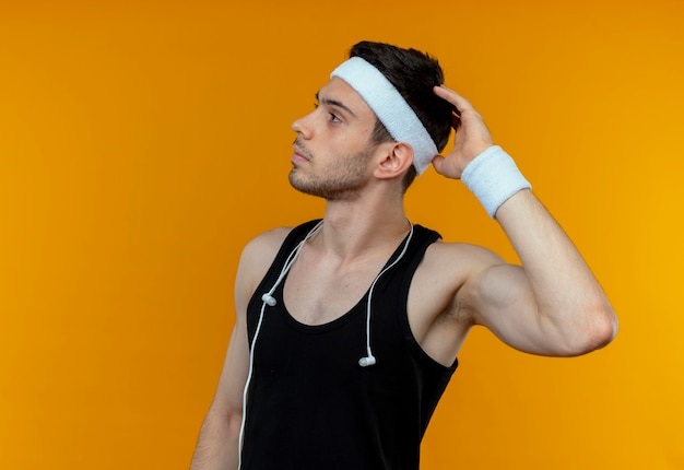 Young sporty man in headband looking aside puzzled scratching his head standing over orange wall