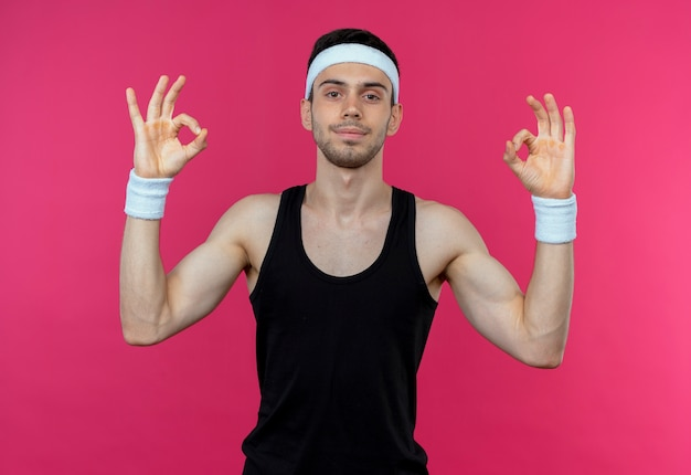 Young sporty man in headband  smiling doing meditation gesture with fingers standing over pink wall