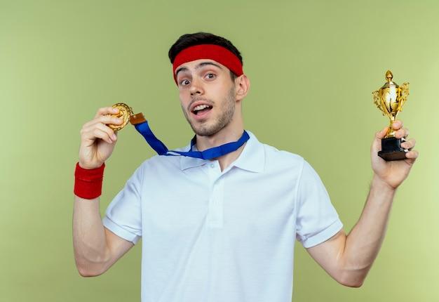 Giovane uomo sportivo in fascia con medaglia d'oro al collo che tiene il suo trofeo in piedi felice ed eccitato su sfondo verde