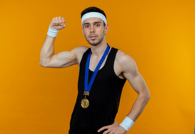 Young sporty man in headband with gold medal around neck looking at camera raising fist with serious expression standing over orange background