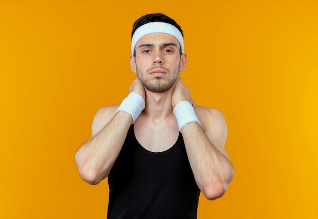Giovane uomo sportivo in fascia con la faccia seria che tocca il suo collo in piedi sopra la parete arancione