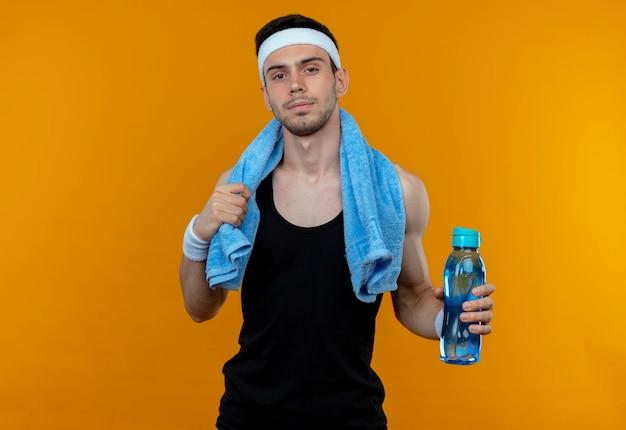 Giovane uomo sportivo in fascia con un asciugamano intorno al collo tenendo la bottiglia di acqua che guarda l'obbiettivo con espressione fiduciosa in piedi su sfondo arancione