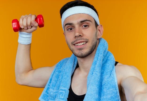 Giovane uomo sportivo in fascia con un asciugamano intorno al collo tenendo il manubrio guardando la fotocamera con il sorriso sul viso in piedi su sfondo arancione