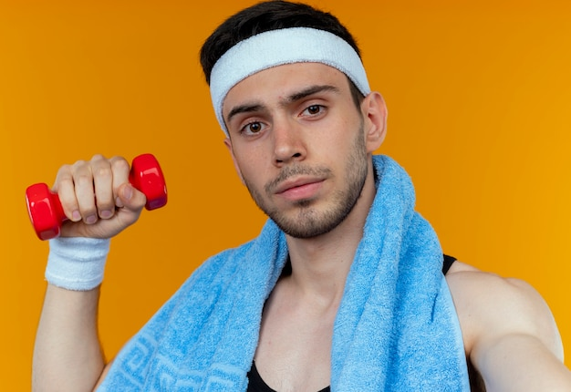 Young sporty man in headband with towel around neck holding dumbbell in raised hand looking at camera with serious face standing over orange background
