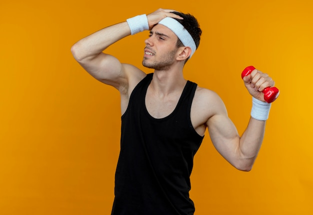 Young sporty man in headband working out with dumbbell looking confused and very anxious over orange
