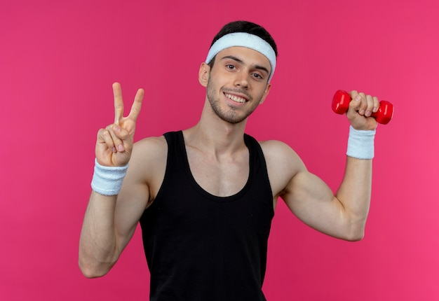 Young sporty man in headband working out with dumbbell smiling showing victory sign over pink