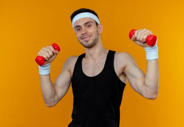 Giovane uomo sportivo in fascia che risolve con i dumbbells che sorridono sopra l'arancio