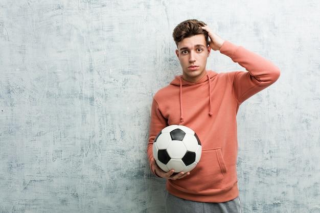 ショックを受けているサッカーボールを保持しているスポーティな若者、彼女は重要な会議を覚えています。