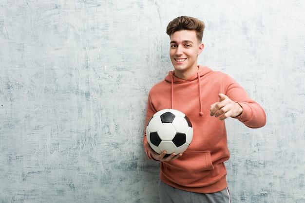 축구 공을 들고 스포티 한 젊은이 앞을 가리키는 밝은 미소.