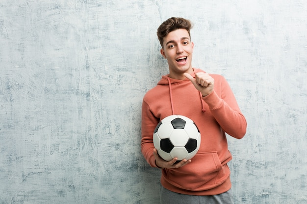 Young sporty man holding a soccer ball smiling cheerfully pointing with forefinger away