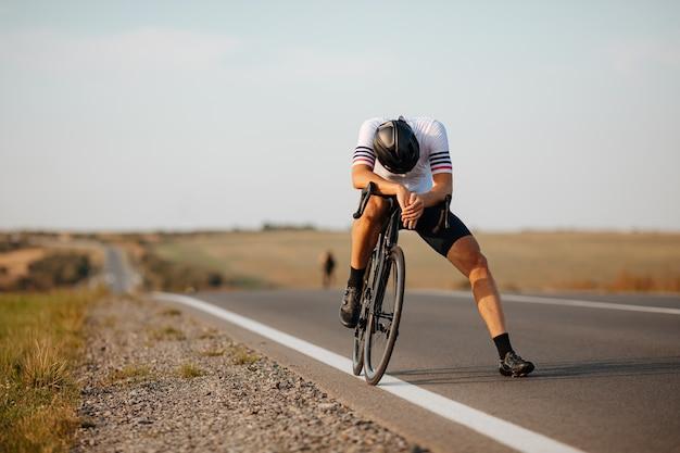 포장 된 도로에서 긴 자전거를 타면 피곤한 검은 헬멧에 스포티 한 젊은이