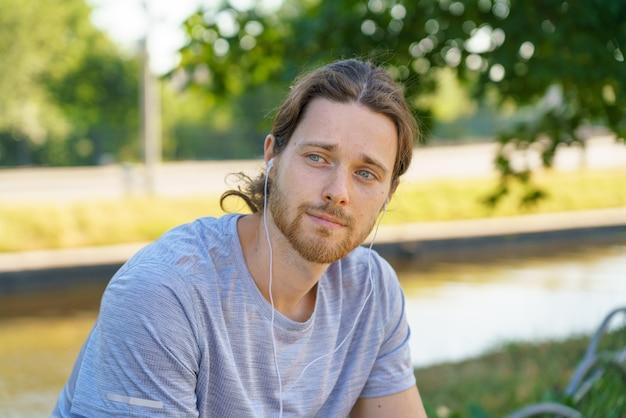 Молодой спортивный человек в наушниках слушает музыку во время отдыха после тренировки на открытом воздухе