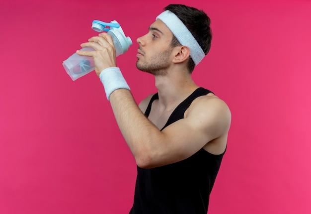 분홍색 벽 위에 서있는 운동 후 머리띠 식수에 스포티 한 젊은이