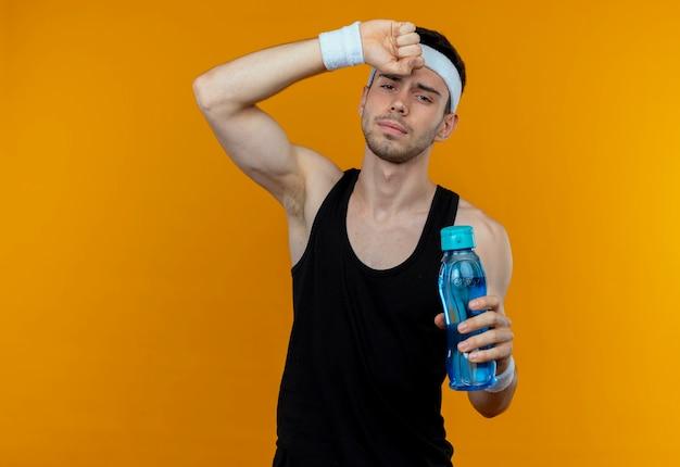 オレンジ色の背景の上に立ってトレーニング後に疲れ果てているように見える水のボトルを保持しているヘッドバンドの若いスポーティな男