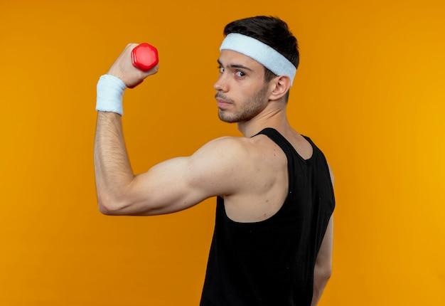 Молодой спортивный мужчина в повязке на голову, держащий гантели, делает упражнения, уверенно выглядит, стоя над оранжевой стеной