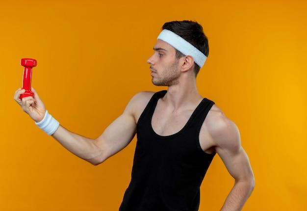 オレンジ色の壁の上に立っている深刻な顔でそれを見てダンベルを保持しているヘッドバンドの若いスポーティな男