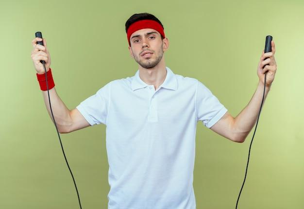 緑の上で疲れて疲れているように見える縄跳びを保持しているヘッドバンドの若いスポーティな男