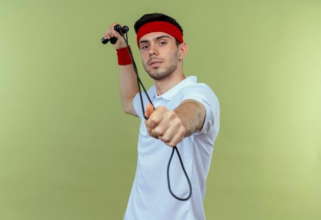 緑の上に自信を持って見えるカメラに人差し指で縄跳びを指しているヘッドバンドの若いスポーティな男