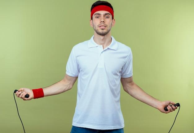 緑の背景の上に立ってジャンプする準備ができて縄跳びを保持しているヘッドバンドの若いスポーティな男