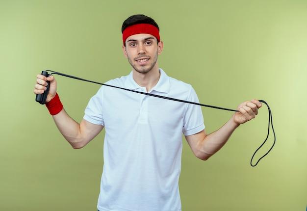緑の上に笑みを浮かべて縄跳びを保持しているヘッドバンドの若いスポーティな男