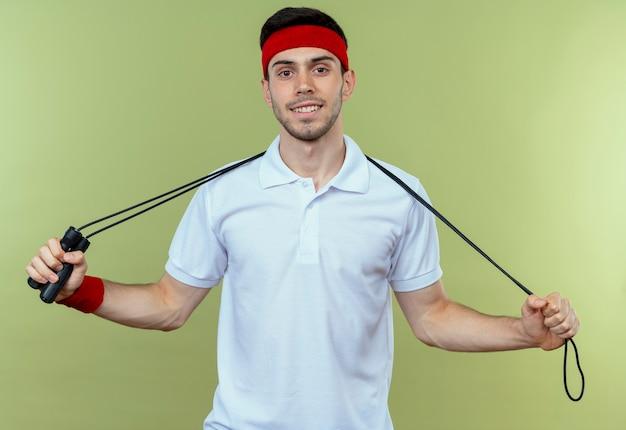 緑の上の顔に笑顔で縄跳びロープを保持しているヘッドバンドの若いスポーティな男