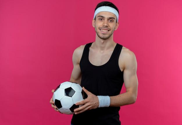 Молодой спортивный мужчина в повязке на голову держит футбольный мяч, весело улыбаясь, стоя над розовой стеной