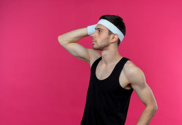 ピンクの壁の上に立っている彼の頭の上の手と混同して脇を見てヘッドバンドの若いスポーティな男