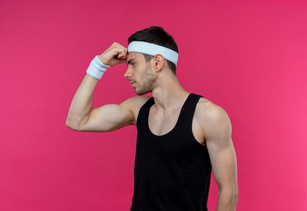 분홍색 배경 위에 서있는 자신감있는 표정으로 팔뚝을 옆으로 보여주는 머리띠에 스포티 한 젊은이