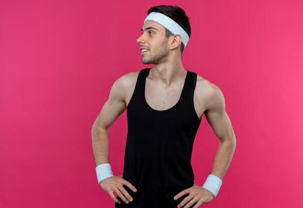 Молодой спортивный мужчина в повязке на голову, глядя в сторону руками на бедре, улыбаясь, стоя над розовой стеной