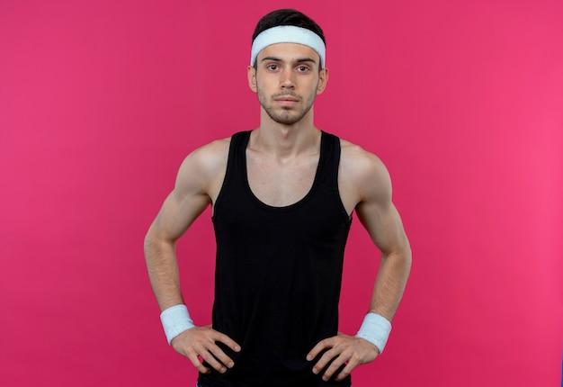 분홍색 배경 위에 엉덩이 서에서 팔을 가진 심각한 얼굴로 카메라를보고 머리띠에 스포티 한 젊은이