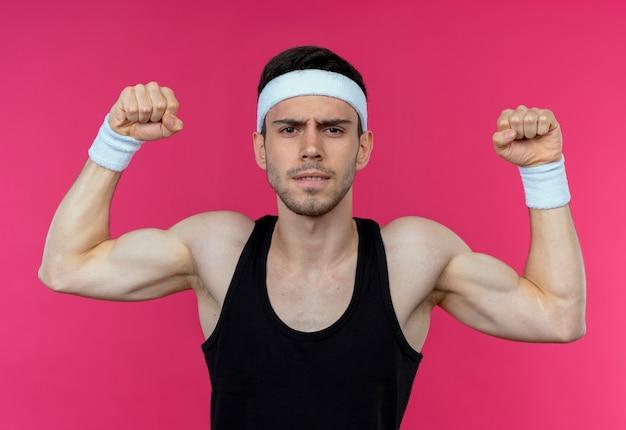 ピンクの背景の上に立っている運動選手のようにポーズをとって緊張した上げこぶしを探しているヘッドバンドの若いスポーティな男