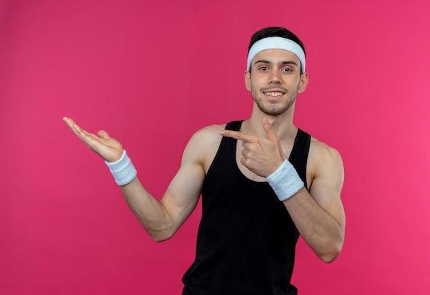 ピンクの壁の上に立っている側に指で指している彼の手の腕で何かを提示するヘッドバンドの若いスポーティな男