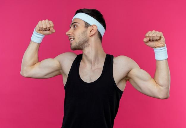 上腕二頭筋、ピンクの背景の上に立っている勝者の概念を示す拳を上げるヘッドバンドの若いスポーティな男