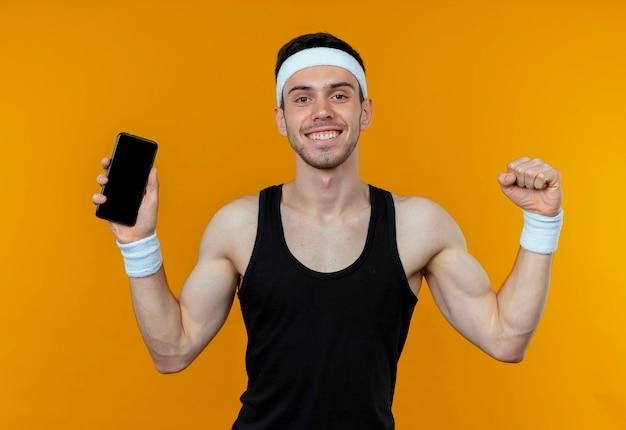 オレンジ色に幸せで興奮しているスマートフォンの握りこぶしを示すヘッドバンドの若いスポーティな男