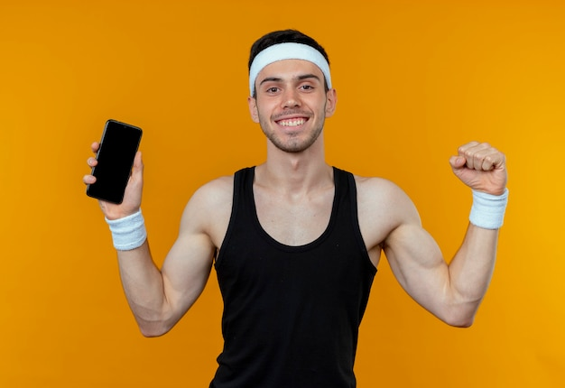オレンジ色の壁の上に立って幸せで興奮して拳を握りしめるスマートフォンを示すヘッドバンドの若いスポーティな男