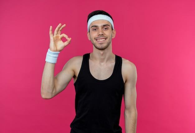 ピンクの壁の上に立っているokサインを示して幸せで前向きに笑ってヘッドバンドの若いスポーティな男