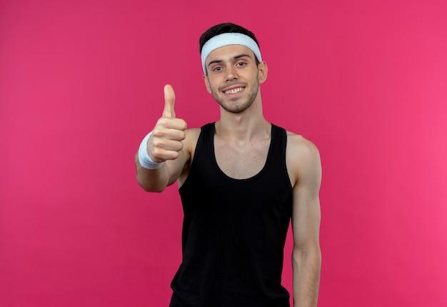 핑크 위에 행복하고 긍정적 인 보여주는 엄지 손가락을 웃는 머리띠에 스포티 한 젊은이