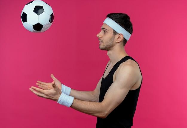 ピンクの背景の上に横に立ってサッカーボールを投げるヘッドバンドの若いスポーティな男