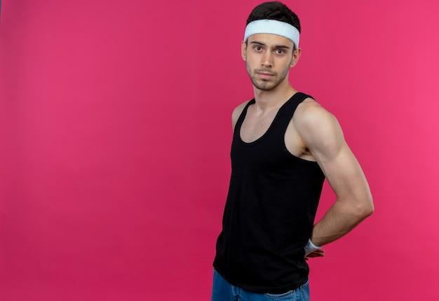 Молодой спортивный мужчина в повязке на голову с уверенным серьезным выражением лица над розовым