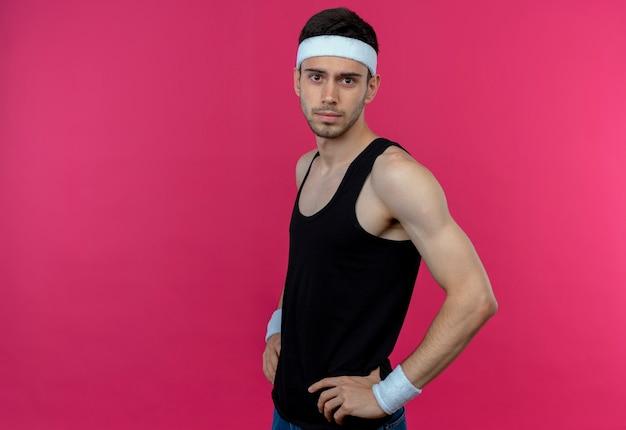 Молодой спортивный мужчина в повязке на голову с уверенным серьезным выражением лица с руками на бедрах, стоящим над розовой стеной