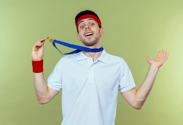 首の周りに金メダルを持ったヘッドバンドの若いスポーティな男は幸せで緑に興奮しています