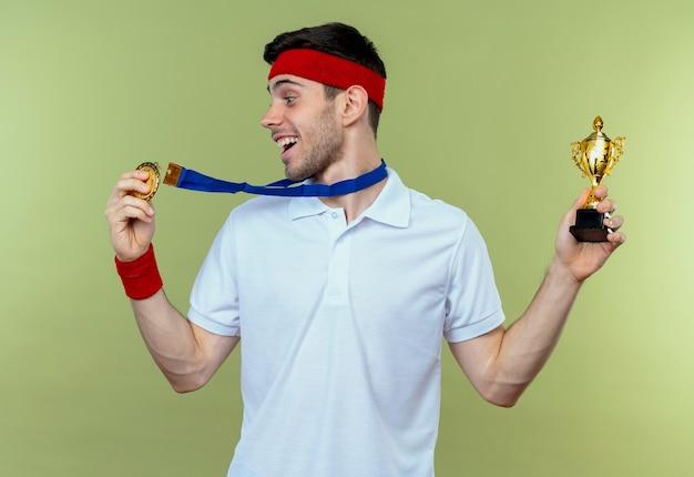 首の周りに金メダルを持ったヘッドバンドの若いスポーティな男が彼のトロフィーを幸せで緑に興奮させています