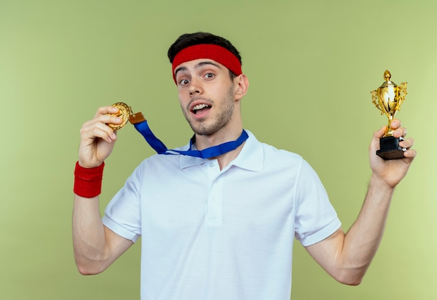 緑の背景の上に立って幸せで興奮して彼のトロフィーを保持している首の周りに金メダルを持つヘッドバンドの若いスポーティな男
