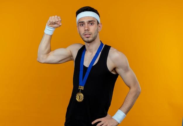 オレンジ色の背景の上に立っている真剣な表情で拳を上げるカメラを見て首の周りに金メダルとヘッドバンドの若いスポーティな男