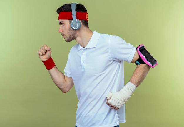 緑の上で懸命に働いているヘッドフォンとスマートフォンの腕章を持つヘッドバンドの若いスポーティな男