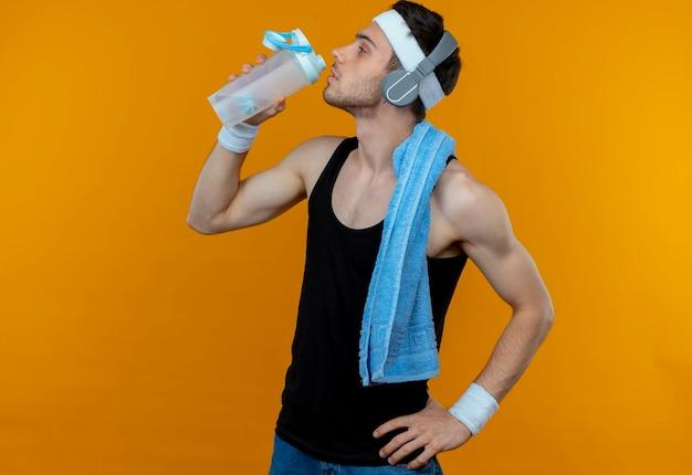 오렌지 이상 운동 후 목 driking 물 주위에 수건으로 머리띠에 젊은 스포티 한 남자