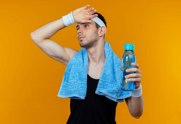 オレンジ色のトレーニング後に疲れて疲れ果てた水のボトルを保持している首の周りにタオルでヘッドバンドの若いスポーティな男
