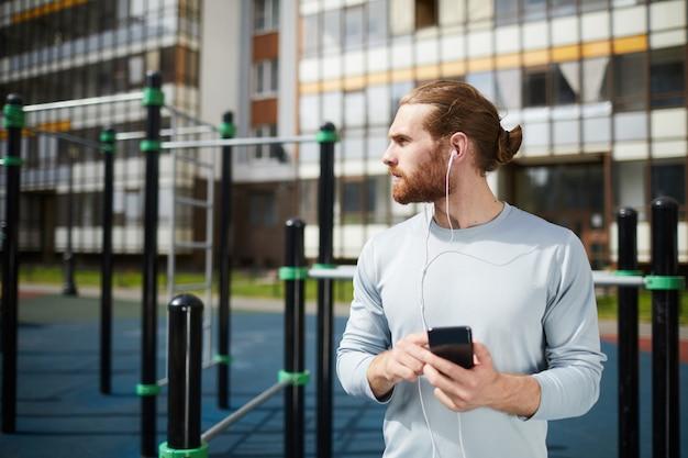 スポーツ地面で音楽を聴く若いスポーティな男