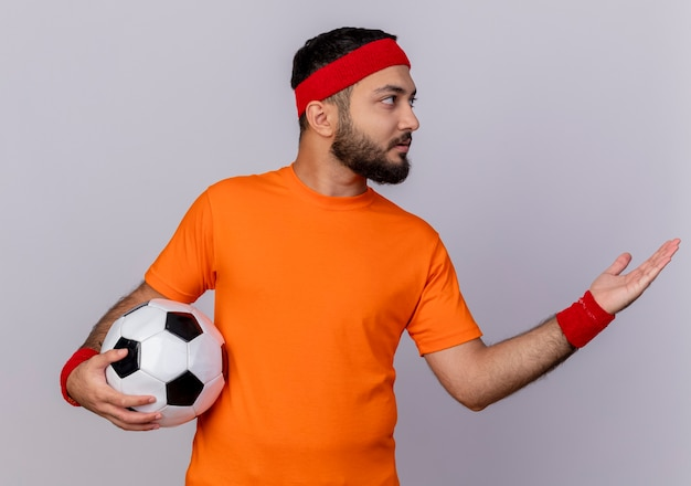 Young sporty man looking at side wearing headband and wristband holding ball and points with hand at side isolated on white background