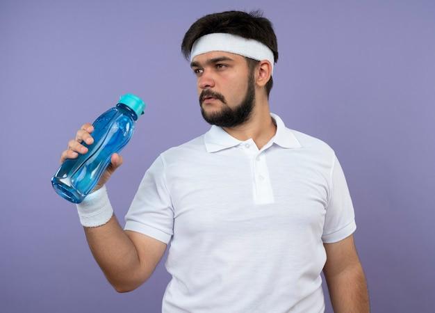 Giovane uomo sportivo guardando lato indossando la fascia e il braccialetto tenendo la bottiglia d'acqua isolata sul verde